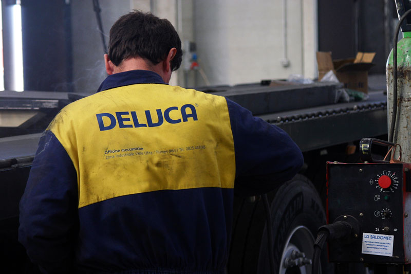Officine De Luca. Employee at work with branded overalls